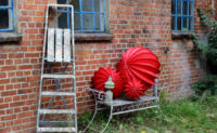 The weatherproof and robust lampion Barlooon as still life in red in sizes S M and L on a garden bench with ladder.