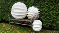 The weatherproof and robust lampion Barlooon as still life in white in sizes S M and L on a garden bench.