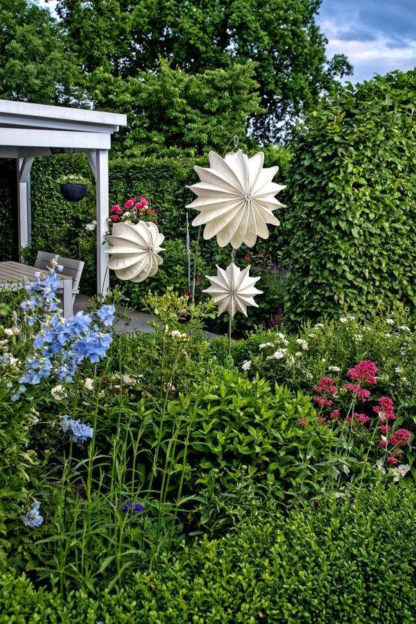 Weatherproof outdoor lampion Barlooon in cream in M and S in the garden.